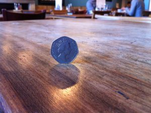 50p coin on cafe table