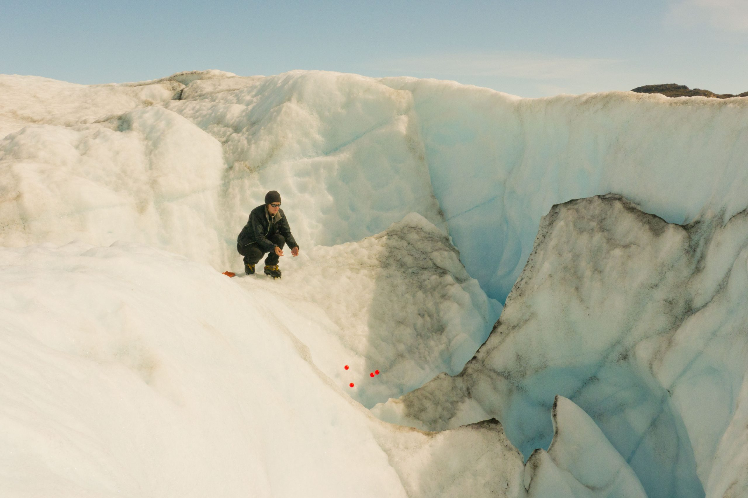 Dr Liz Bagshaw throwing electronic tracers down a moulin. Photo: George Cave for ICE TRACERS.